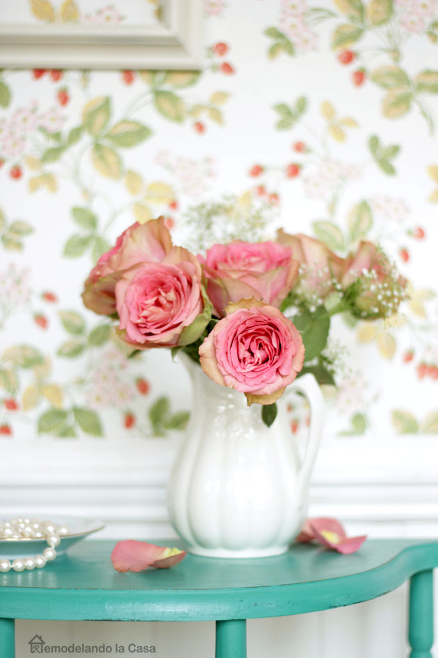 pink roses in white pitcher, pearls, petals on table, floral wallpaper and beadboard