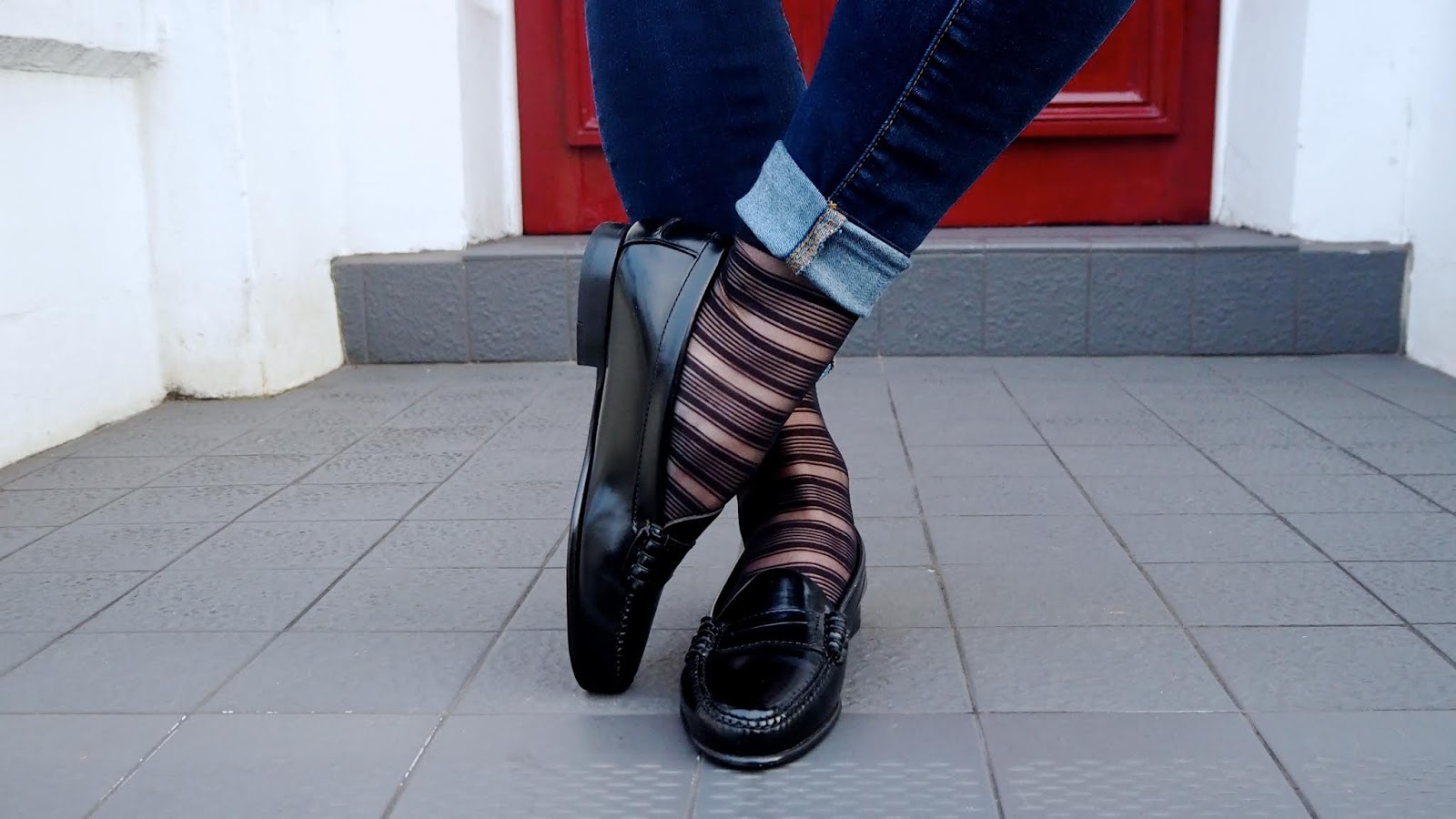 black leather penny loafers with striped sheer socks