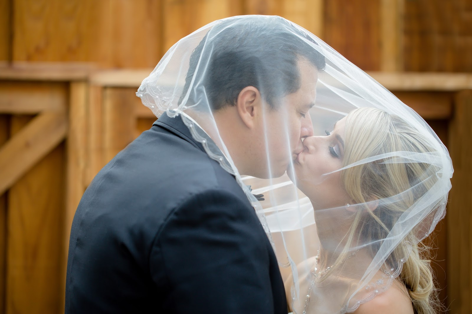 Bride and groom kiss under veil
