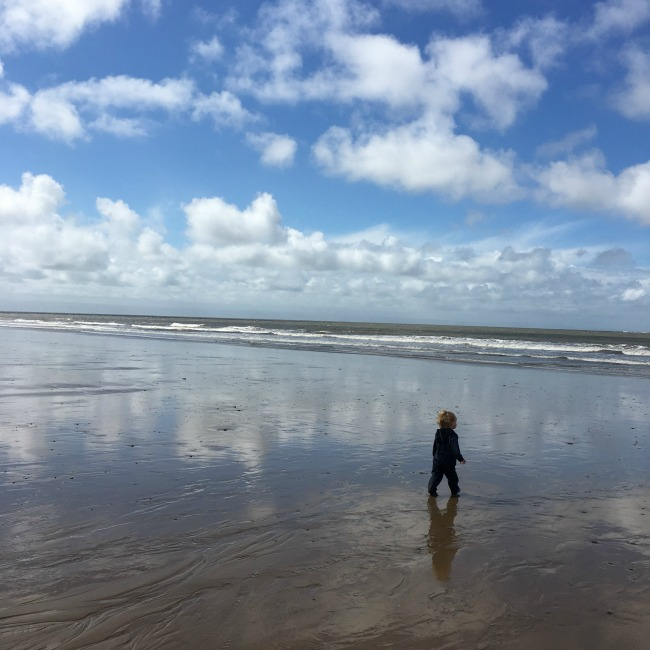 toddler-walking-on-huge-sandy-beach