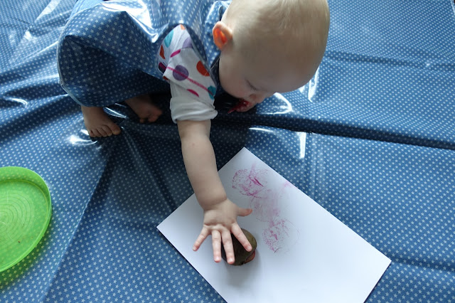 A baby making stamps with cut beetroot on a white piece of card on a wipe clean messy mat in blue with small white stars. Taken further away than the previous shot so you can see more of the baby.