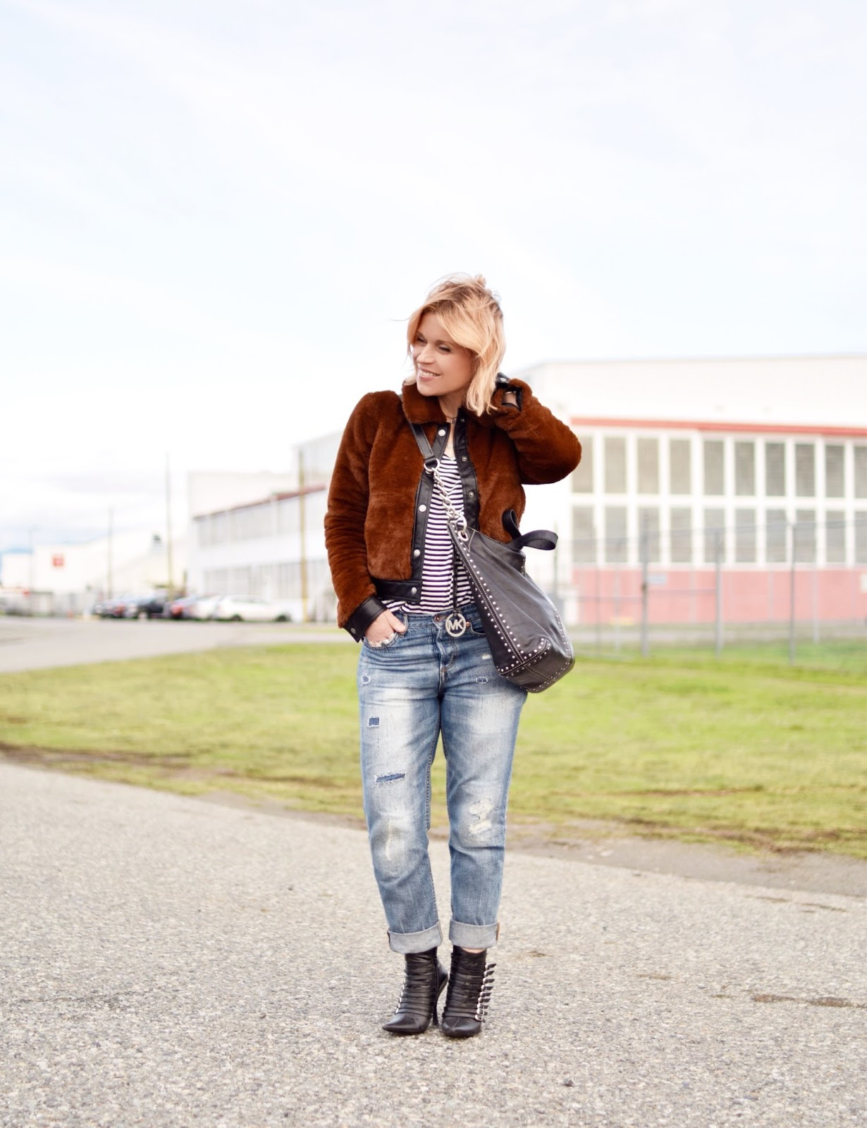 Monika Faulkner outfit inspiration - styling a faux-fur bomber with a striped tee, boyfriend jeans, and stiletto booties