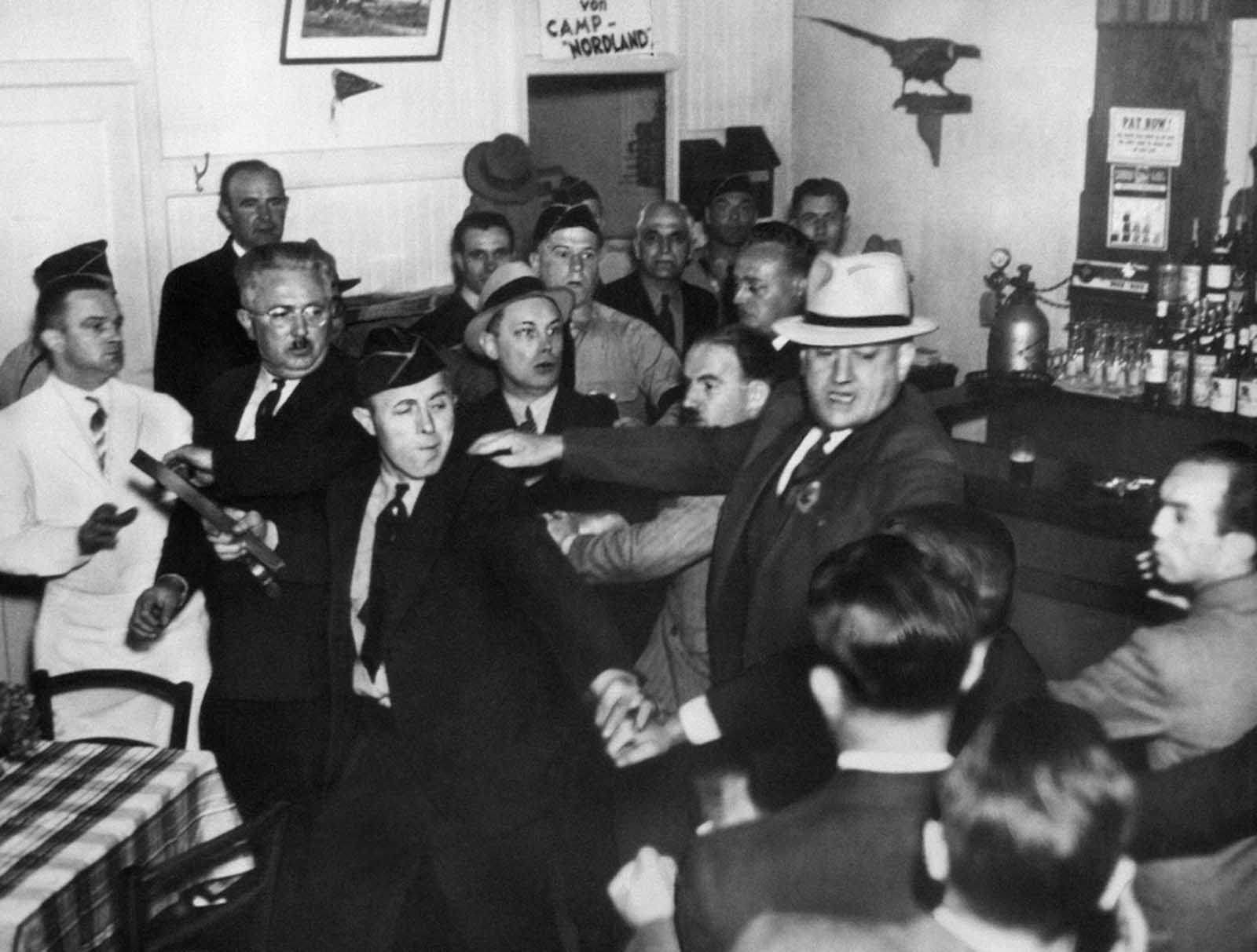 "An anti-Nazi crowd rushed the bar entrance of the German-American Bund Hall in Union City, New Jersey, on October 2, 1938 where Fritz Kuhn, bunds-fuehrer, was to make a ""victory"" speech celebrating Hitler's occupation of Czechoslovakia. Bund members, including one with a belt as weapon drove the protesters out, but the meeting was disrupted."