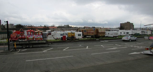 Mobile homes parked on a grassy area near a main road
