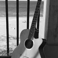 b&w of guitar with beach background