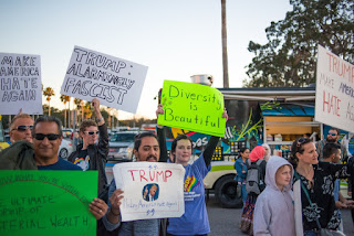 Protesters hold signs during the Donald Trump visit to USF Tampa, FL.