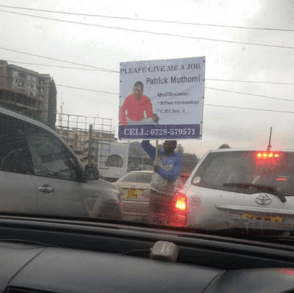Unemployed graduate seeks for job using a huge placard with his photo