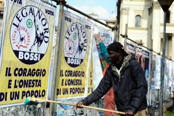 [Immagine: immigrato+con+manifesti+leghisti.jpg]
