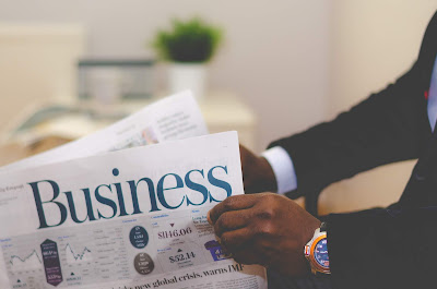 black man's hands holding a Business newspaper