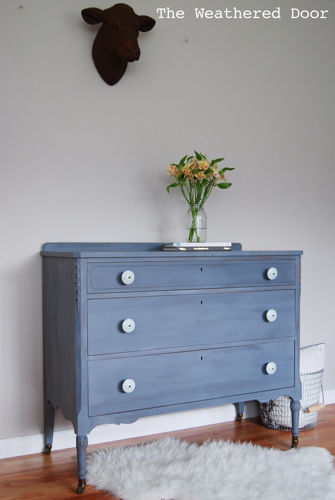 a grey blue purple dresser with soft blue knobs the weathered door