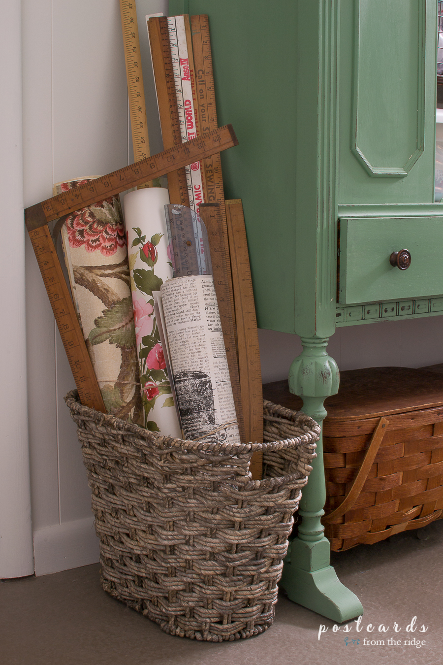 Vintage yardsticks and wallpaper pages in a woven basket