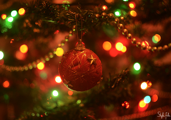Image of a red velvet ornament hanging on a Christmas tree with gold beads and fairy lights with bokeh in the background