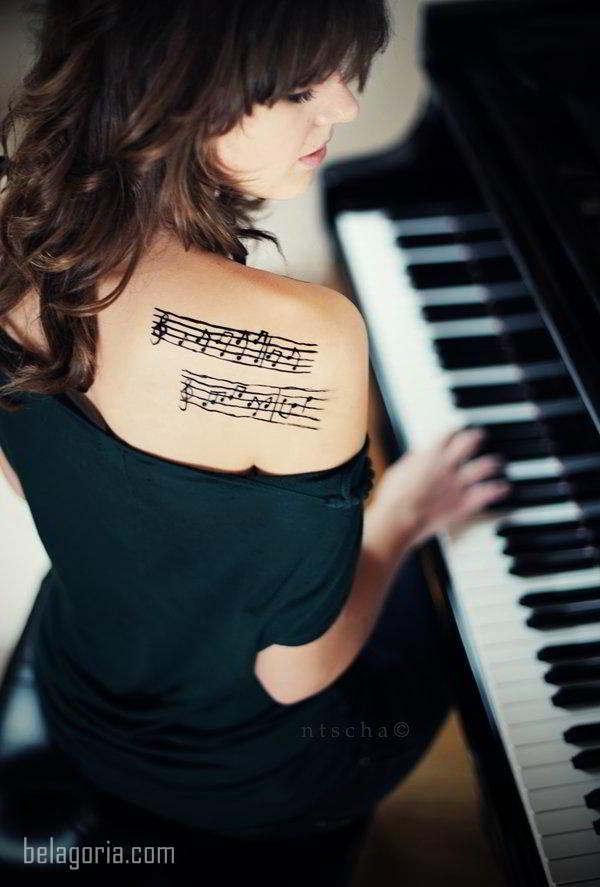 vemos a una pianista con tatuaje de partitura en el omoplato