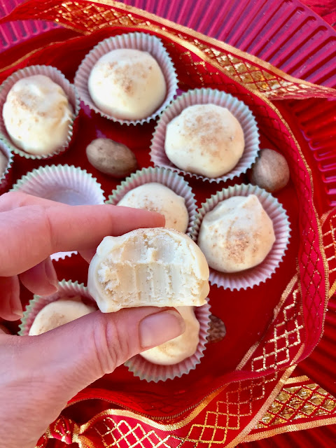 Platter of finished eggnog truffles with a hand holding one showing a bite out.