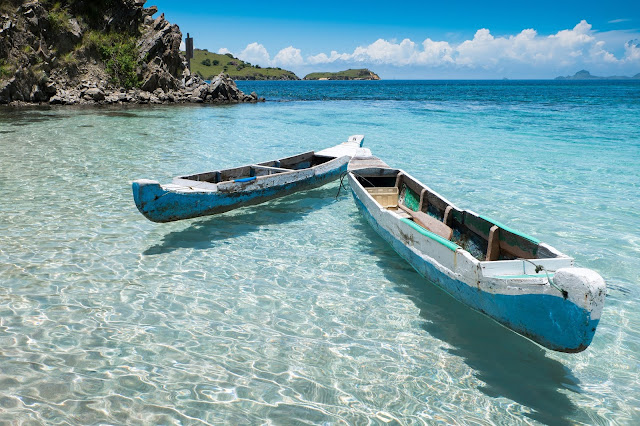 Two wooden paddles boats on a super clear sea with rocky shore in the background