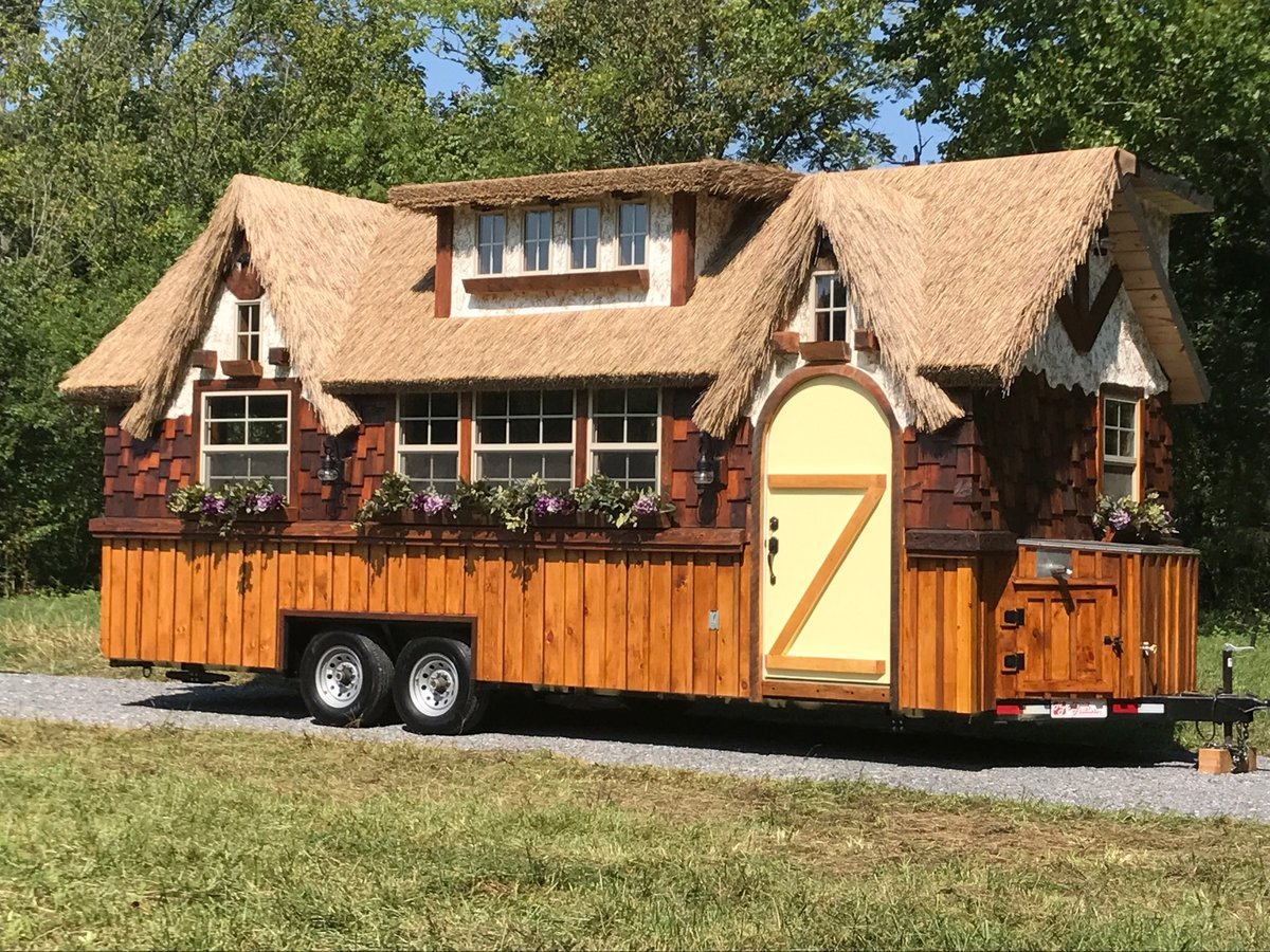 01-Exterior-View-The-Highland-Tiny-Home-on-wheels-with-Thatched-Roof-www-designstack-co