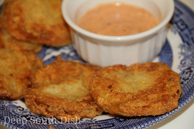 Fried green tomatoes dipped in milk, then dredged in a combination of flour, cornmeal and crumbled saltine crackers, then pan fried.