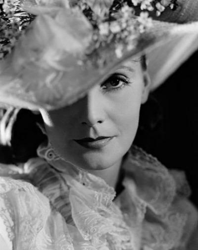 Greta Garbo in screen shot from Anna Karenina wearing an elaborately decorated Adrian designed hat