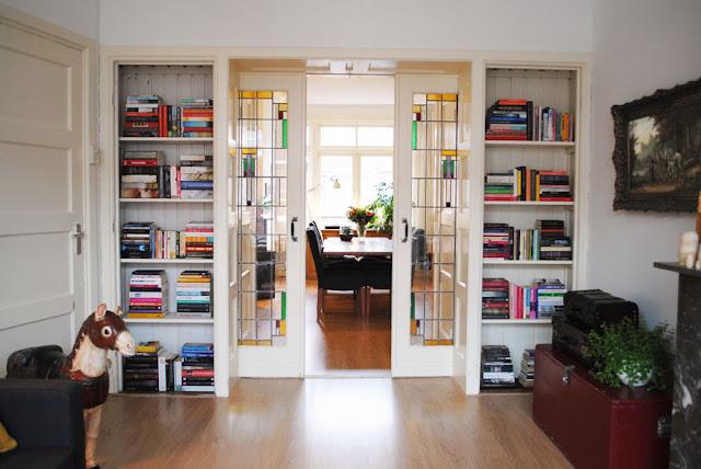 Twee en suite deuren met glas in lood in de zitkamer met aan beide zijden ingebouwde boekenkasten.
