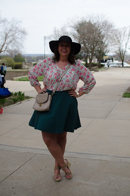 an outfit with a floral blouse, green skater skirt, taupe purse, taupe wedges, and a black hat