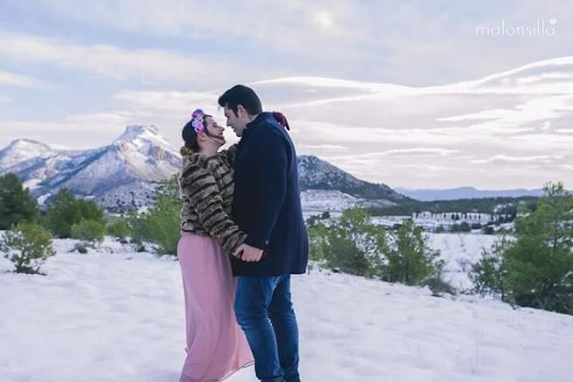 Pareja en la nieve con tocado de flores, vestido rosa y abrigo
