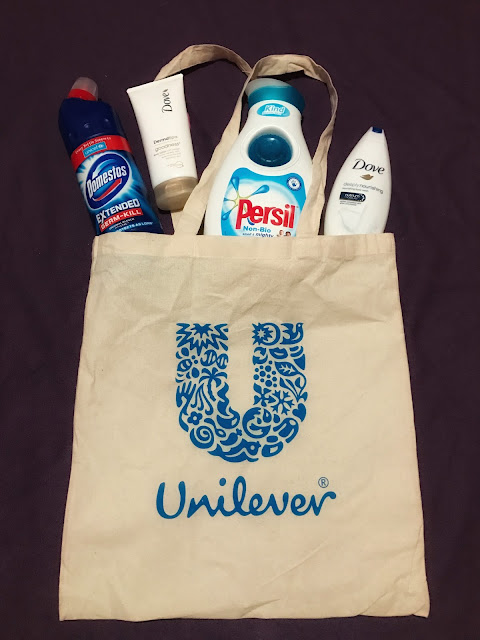 "A fabric bag with a ""U"" on and the Unilever logo with a bottle of Domestos, Dove body lotion, persil non bio and Dove bath cream"