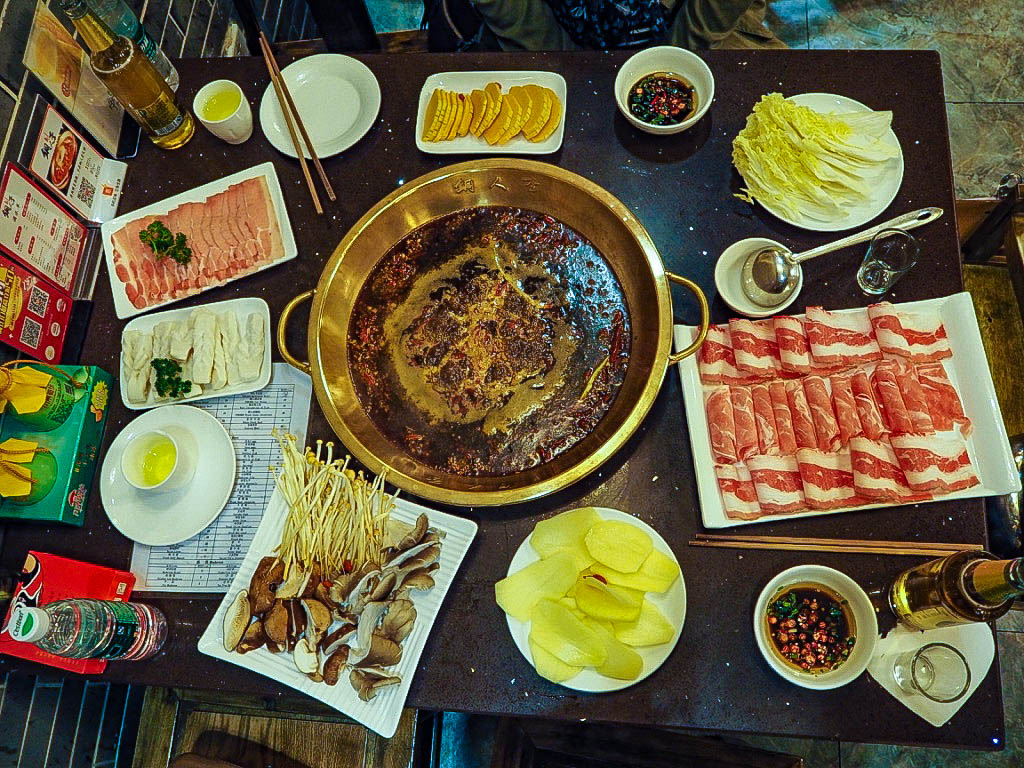 Chinese hotpot with vegetables and raw meats