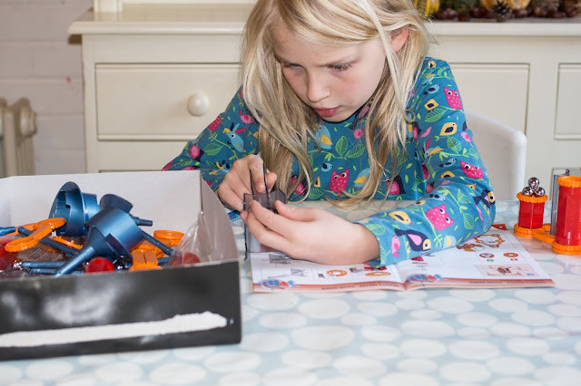A young girl focusing on assembling 2 pieces of plastic for the Geomag gravity motor