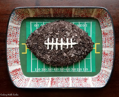 cookies and cream cheese ball shaped like football on a football field platter