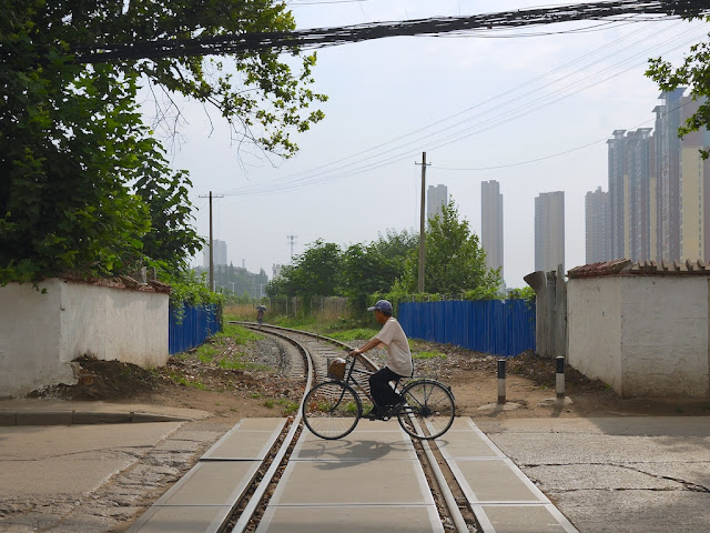 man riding a bike over a railroad track in Bengbu