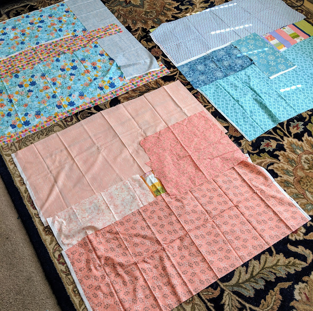 Three small tops are laid out so backing fabric can be properly sized. The fabrics are grouped by color to create monochromatic backs in blue or peach.