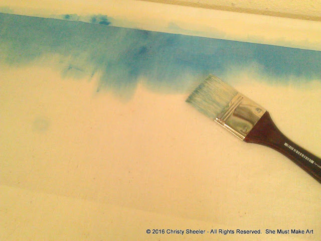 First brushstrokes of watercolor with a wide brush on fabric.