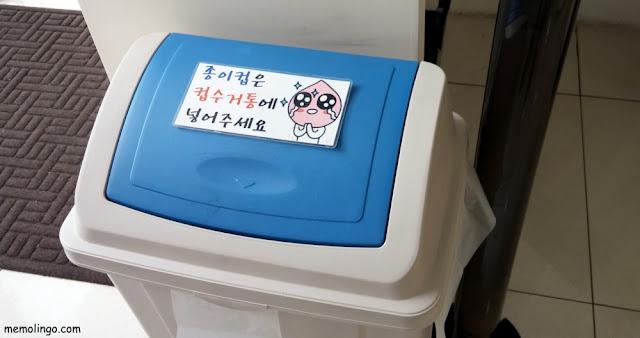 Papel en coreano pegado en una papelera