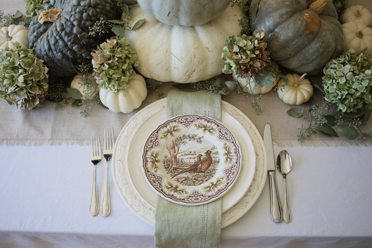 neutral fall tablescape with partridge plates hydrangeas and green pumpkins