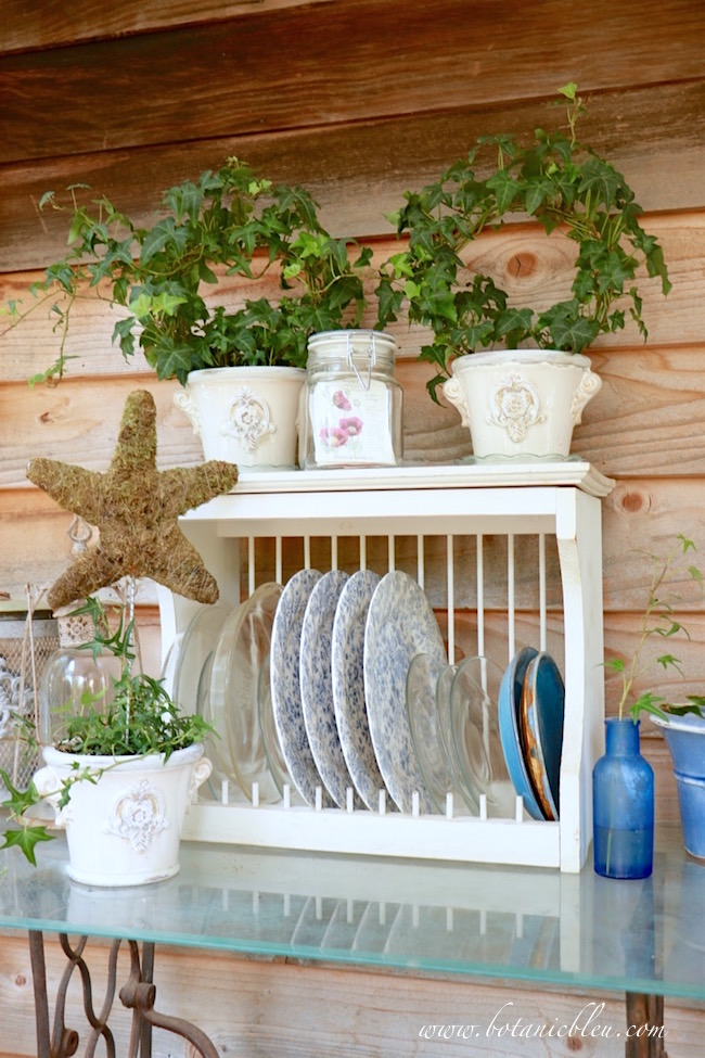 white-wood-plate-rack-holds-blue-floral-dishes-ivy-wreaths