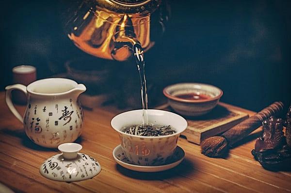 Chá verde. colocando chá na xícara