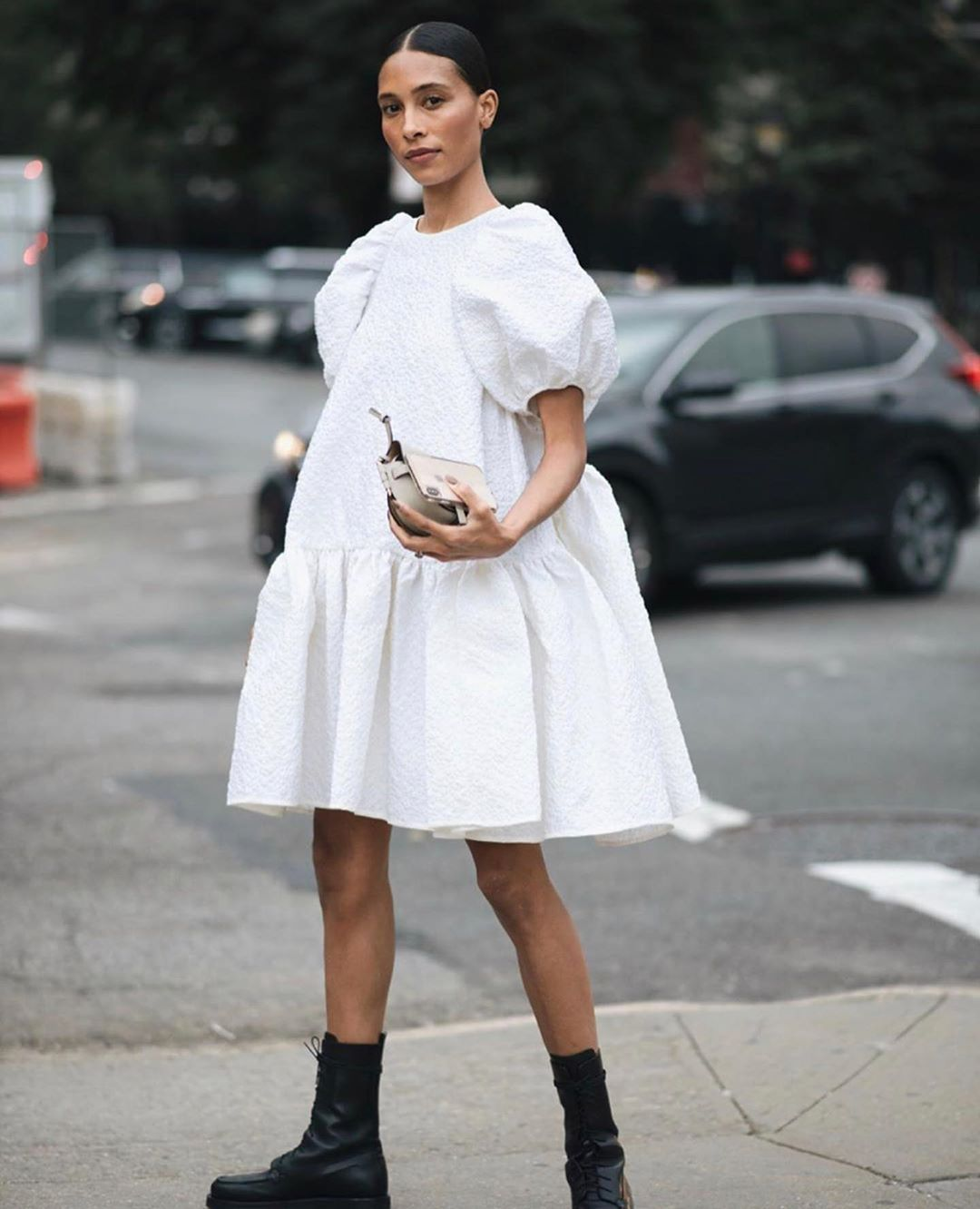 Tylynn Nyugen in a Cecilie Bahnsen puff-sleeve white dress with black combat boots