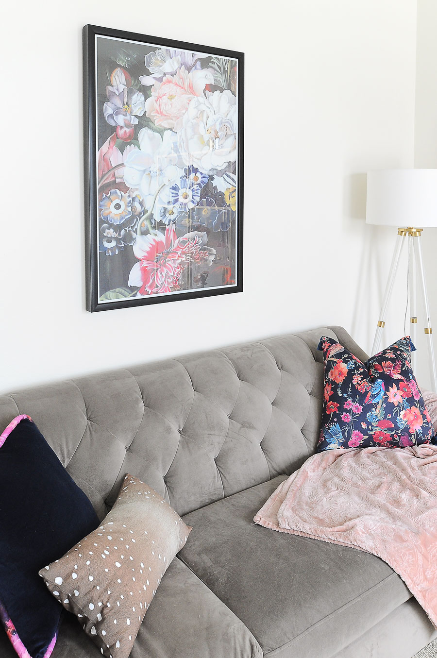 A floral art print adds color and a feminine touch to a home office with white and gold touches.