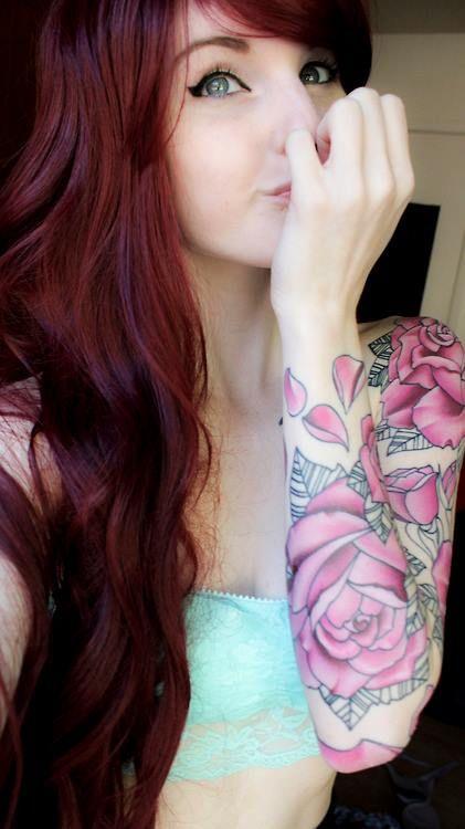 Linda peliroja con tatuajes de flores rosas en su brazo