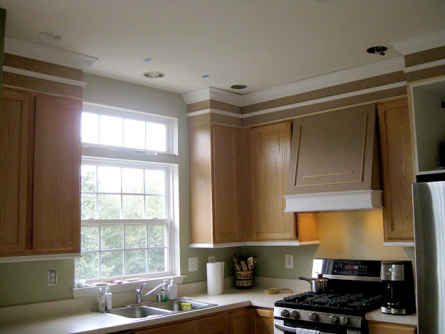 Give new life to oak cabinets with moldings, a builder's grade basic kitchen is transformed with crown molding, under cabinet moldings and paint