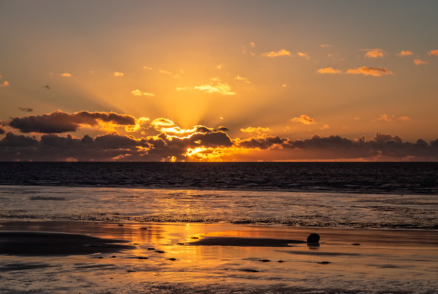 Photo of the sun setting on the shore at Maryport