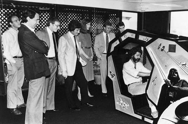 George Lucas trying the sit down version of the Star Wars Arcade Machine