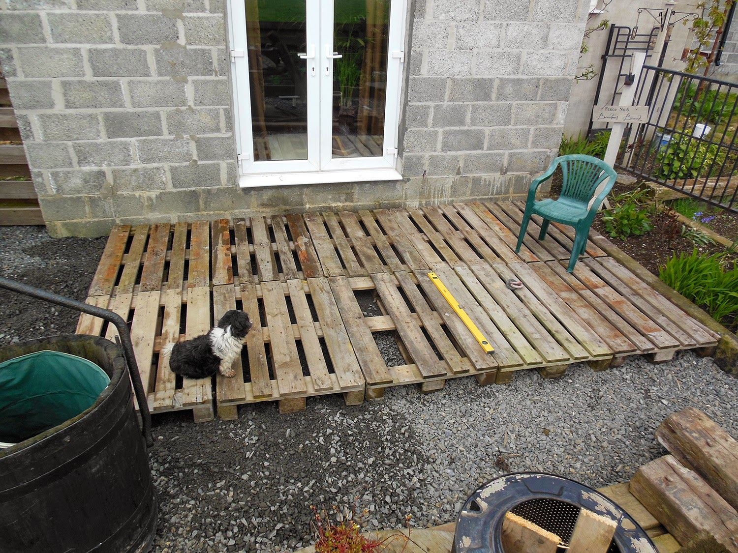 Coach house crafting on a budget diy pallet wood decking for Decking framework timber