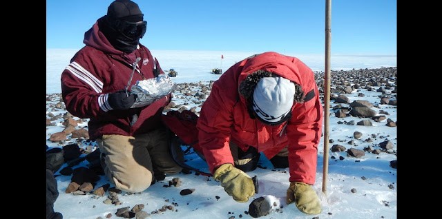 Members of the Antarctic Search for Meteorites (ANSMET) program collect a carbonaceous chondrite meteorite from a glacial moraine at the base of Mt. Ward, Antarctica. Credits: Christine Floss