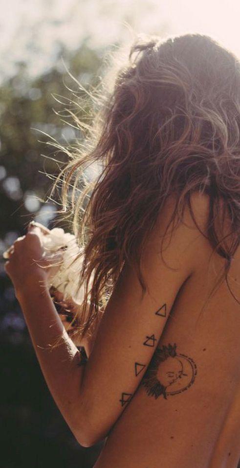 Chica hippie con tatuaje de cuatro triangulos en el brazo