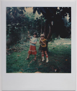 kids playing by a tree with a rope tied to it