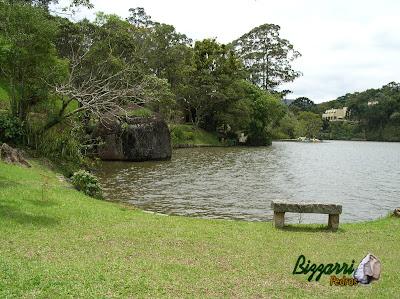 Construção de lagos com muros de pedra com o banco de pedra e o paisagismo.