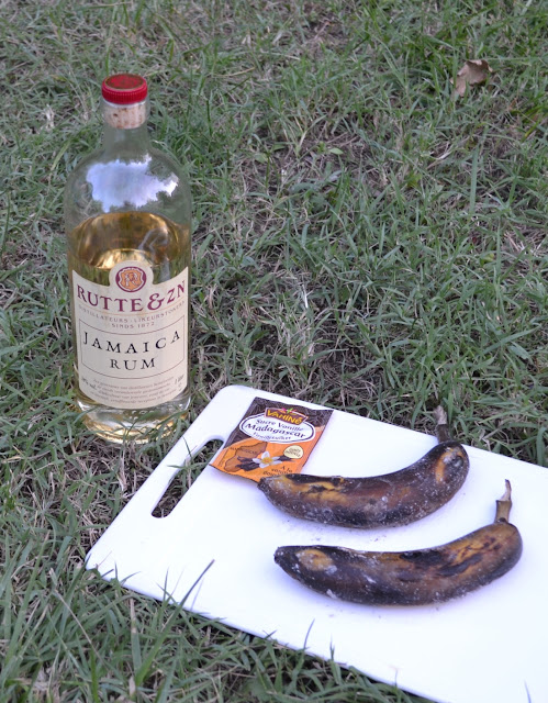 een fles Jamaica rum van Rutte, een zakje vanillesuiker en 2 gebarbecuede bananen in schil op een snijplank