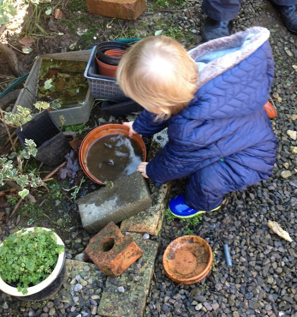 toddler picking up plant pots with muddy water in