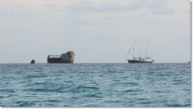 The ruins of SS Sapona  and large sailboat sit on the ocean horizon